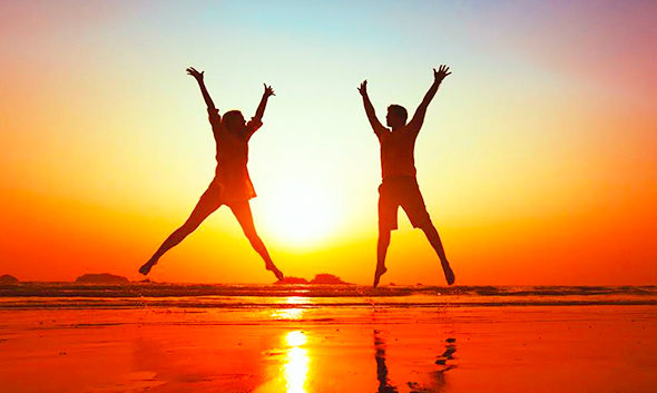 Image of two people jumping silhouetted by a sunset on the beach.