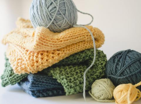 Image of piled knitting projects and yarn.